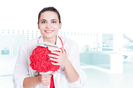 Friendly and happy doctor holding a bouquet of roses and money in her office with copy space