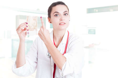 Young woman doctor with euro money pointing finger up as first or financial increase concept