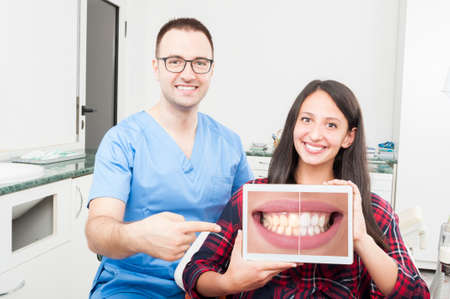 orthodontist: Orthodontist and patient pointing on tablet and smiling