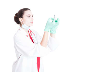 Professional woman doctor getting ready and preparing syringe for vaccine on white studio background with advertising area Stock Photo