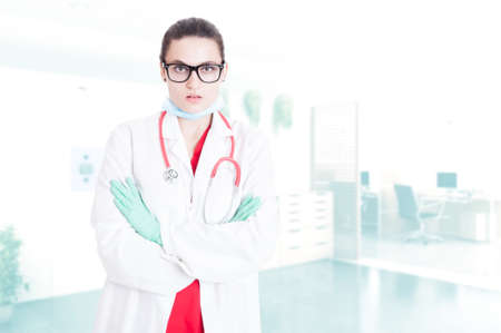Serious doctor in medical unifrom standing with folded arms in her office with advertising area Stock Photo