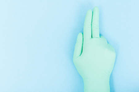 surgical glove: Sterile surgical glove indicate three fingers in closeup on blue background with advertising area