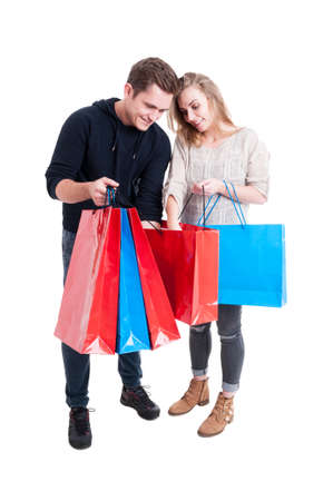 Happy couple looking in shopping bags and smiling isolated on white background