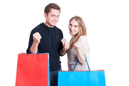 puños cerrados: Pareja con bolsas de compras haciendo gesto que gana con los puños aislados en fondo blanco con espacio de copia de texto