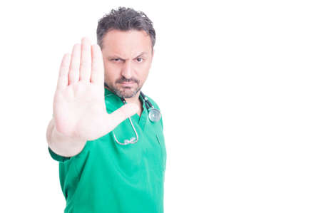 Serious male doctor doing stop gesture with his hand as warning concept isolated on white with copyspace Stock Photo