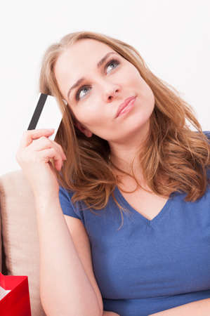 indecisive: Portrait of woman feeling pensive of something holding and credit or debit card  feeling indecisive