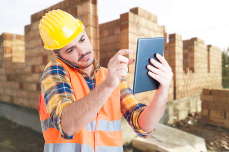 Construction specialist using a tablet computer at a construction site and calling someone as multitasking concept Stock Photo
