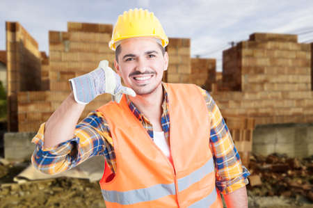 house call: Handsome construction engineer doing a call gesture outdoor in front of building house and smiling