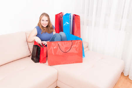 Lady sitting on couch finding things in shopping bags and acting joyful with copy text space