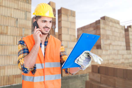 Builder worker with clipboard talking on cellphone in front of building under construction as successful job concept Stock Photo