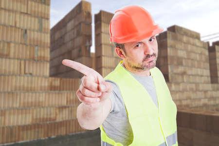 Ernstige bouwer in beschermingsmiddelen het doen van een weigering gebaar tijdens het staan op de bouwplaats Stockfoto
