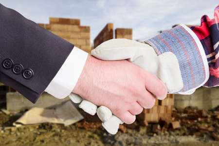 Business handshake in closeup with constructor and businessman as successful construction partnership concept