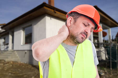 Male engineer or constructor with neck pain looking exhausted after rebuilding house