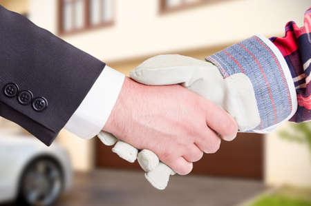 Bouwer schudden klant hand in close-up in de voorkant van het nieuwe huis als huis renovatie begrip