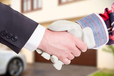Builder shaking customer hand in close-up in front of new house as home renovation concept