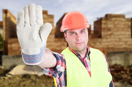 warning vest: Portrait of male builder rising hand and doing stop sign in front of building house Stock Photo