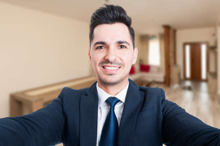 Close-up portrait of estate agent taking a selfie inside of rented house