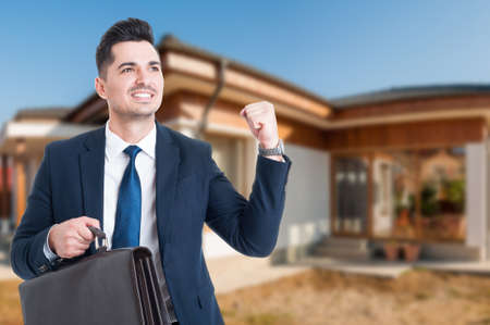 Joyful estate agent enjoying victory while standing in front of rented house with copy space area