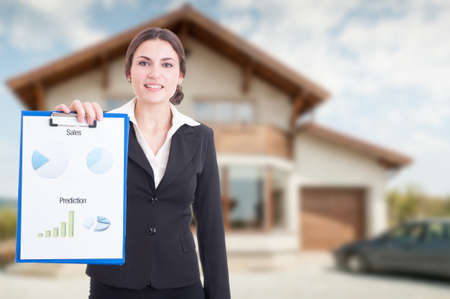 Estate profit concept with female realtor standing outdoors with clipboard with diagrams in hand and advertising area
