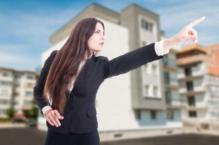 Real estate agent looking and pointing finger at something outside in front of building Stock Photo