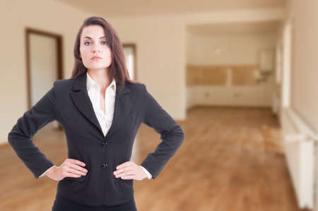 area sexy: Beautiful estate consultant with hands on her waist standing in rented apartment with advertising area Stock Photo