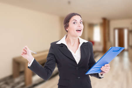 Smiling young realtor writing on clipboard as new rental contract concept