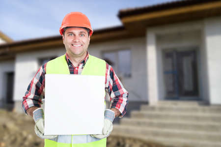 Smiling young builder holding big box on construction site with copy text space Stock Photo