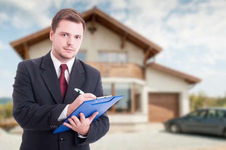 Professional estate seller with clipboard writing documents outside in front of rented house with advertising area Stock Photo