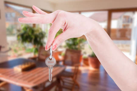 Close-up of female hand holding house key inside of rented property as real estate concept
