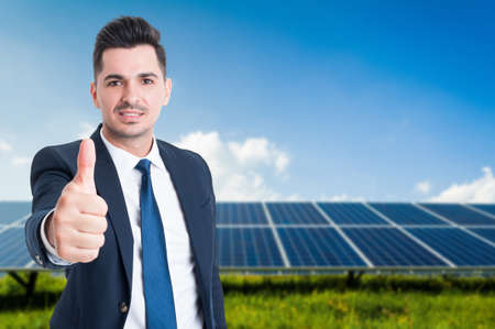 Young businessman in solar power station as ecological energy concept with copy text space