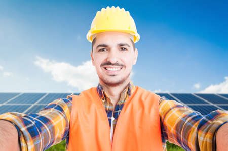 Confident engineer taking a self portrait with ecologic panels in background Stock Photo