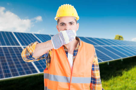 Male constructor in solar station doing speak no evil gesture and covering his mouth Stock Photo
