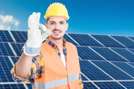 Glücklicher Erbauer am Solargenerator, der das okayzeichen fördert die eco Energie als neue Quelle der Elektrizität tut