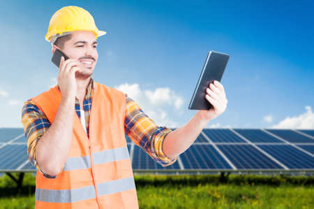 durable: Successful workman on cellphone and tablet in hand making business with solar panels as durable electricity concept