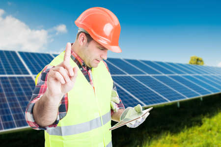 Busy engineer browsing something on tablet about renewable energy with advertising area