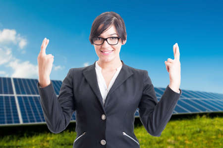 Pretty business woman doing good luck sign with both hands near solar panels