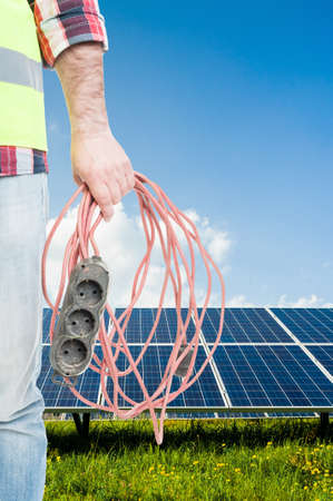 Unknown engineer with extension cord in hand as concept of using solar power as source of energy