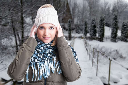 warm jacket: Female model outside in winter park wearing warm jacket, knitted hat and comforter with text space
