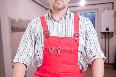 Male plumber with fixing tools in his pocket as repair or installation concept