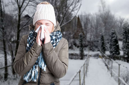 Winter illness concept with woman blowing into napkin outside in the snowy day with copy text space