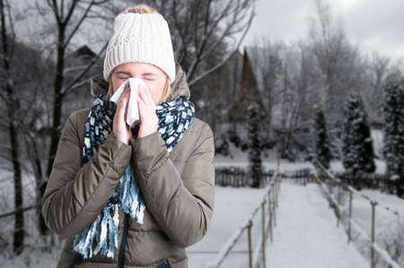 Het concept van de de winterziekte met vrouw die in servet buiten in de sneeuwdag met de ruimte van de exemplaartekst blazen Stockfoto