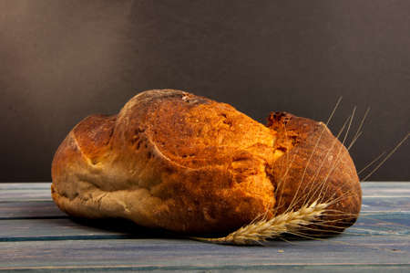 Crispy bread with rye on wooden table in closeup as rustic product concept
