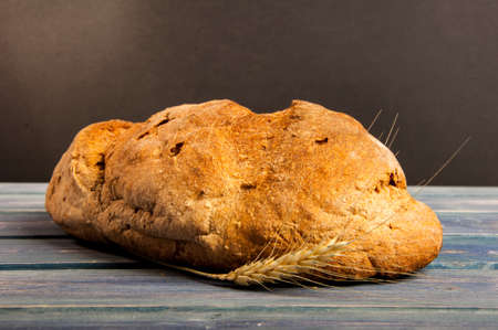 Rustic bread and wheat on vintage wood table in closeup