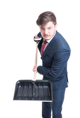 Man wearing suit holding snow shovel looking mad isolated on white background Stock Photo