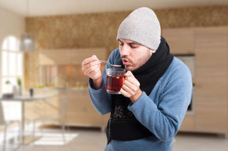 shiver: Handsome young man in winter clothes holding a cup of hot tea as grippe or flu concept with copyspace