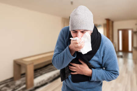tosiendo: Man feeling bad and coughing in a napkin inside the house with advertising area Foto de archivo