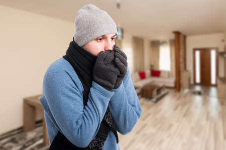 Young man feeling cold and warming his hands inside the house with text area