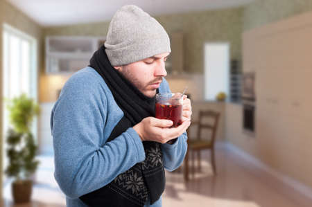 grippe: Male in warm clothes with grippe or influenza drinking hot tea indoors with advertising area