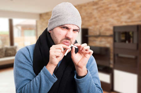 Young man breaking cigarette in two pieces as stop smoking concept