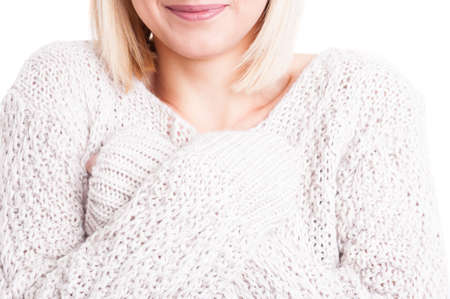 Close-up of woman wearing warm sweter with arms crossedClose-up of pretty woman wearing warm sweter standing with arms crossed and smiling isoalated on white background